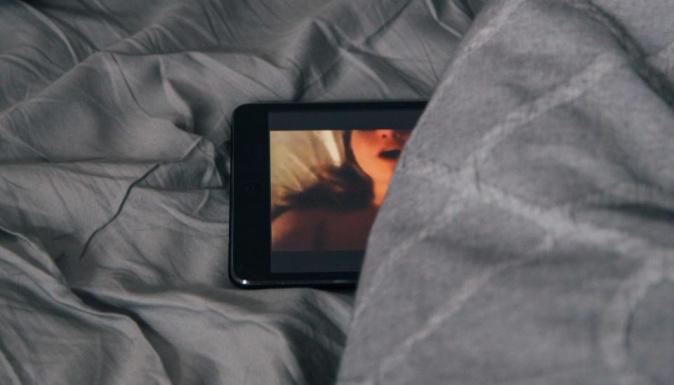 Une tablette est déposée sur un lit, une image de femme apparaît à l'écran.